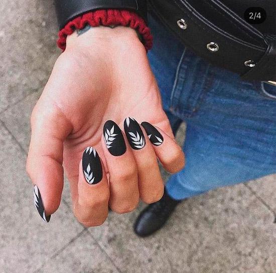 черный матовый маникюр с белыми листьями на овальных ногтях
