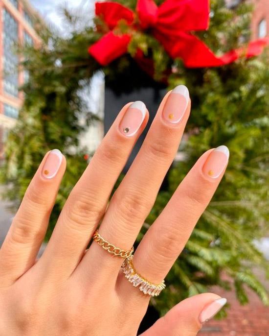Необычный белый френч со стразами на овальных ногтях средней длины