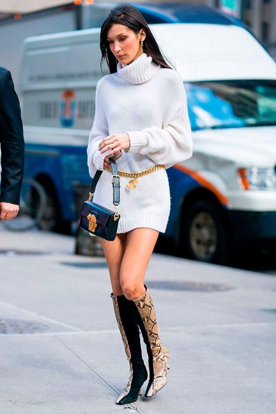 Белла Хадид в белой мини юбке с цепочным ремнем, свитер оверсайз и интересные комбинирование сапоги из змеиной кожи