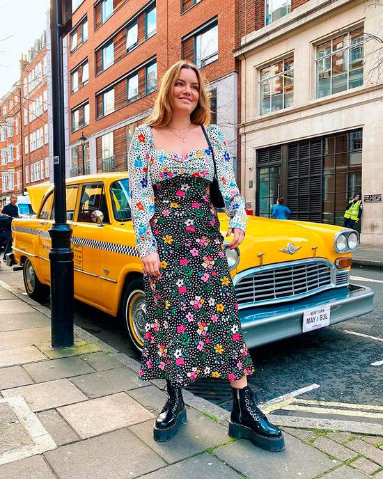 Девушка в платье миди с цветочным принтом, черные ботинки на шнуровке и мини сумочка