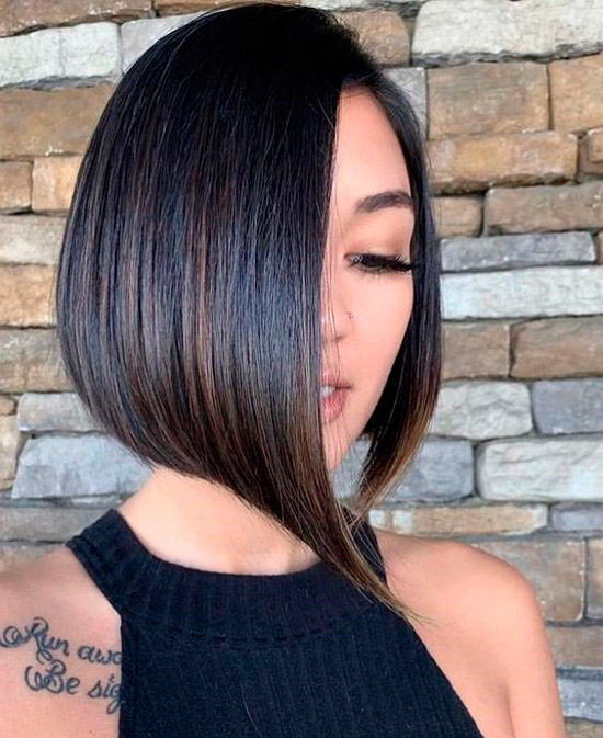 Девушка с асимметричной стрижкой на темных гладких волосах с пробором на одну сторону