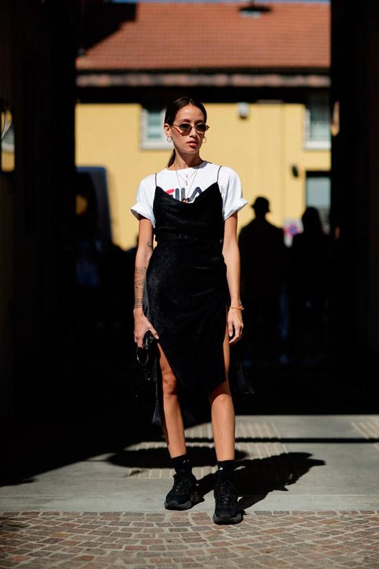 Девушка с белой футболкой с надписью, черное платье комбинация и объемные кроссовки