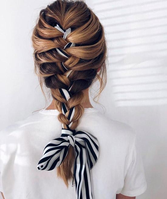 Девушка с французской косой украшенная повязкой на красивых волосах средней длины