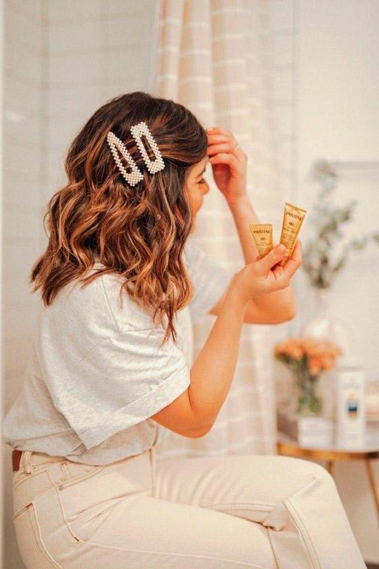 Девушка с легкими волнами на волосах средней длины, украшенные заколками