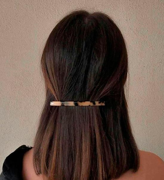 Девушка с натуральными темными волосами собранные простой заколкой