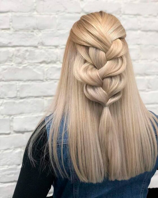 Девушка с пышной косой на светлых гладких волосах
