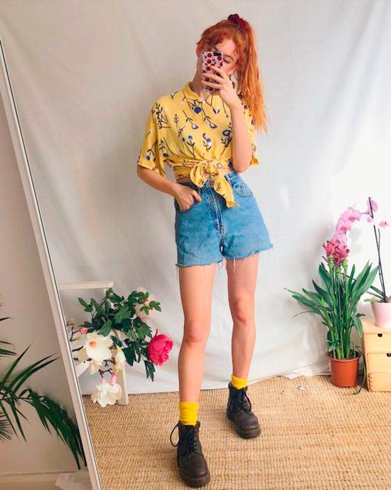 Девушка в джинсовых шортах с высокой талией, желтая рубашка с цветочным принтом и ботинки на шнуровке