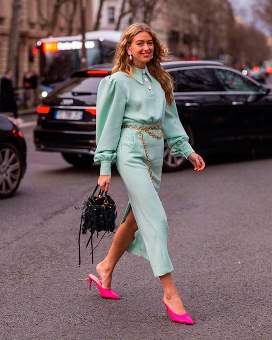 Девушка в голубом платье с цепным ремнем на талии, розовые туфли и оригинальная сумочка дополняют образ