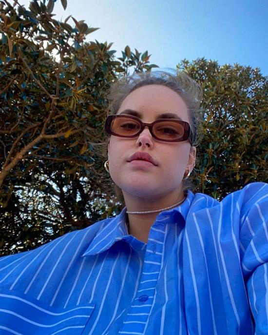 Девушка в голубой рубашке в тонкую полоску и коричневых прямоугольных солнцезащитных очках