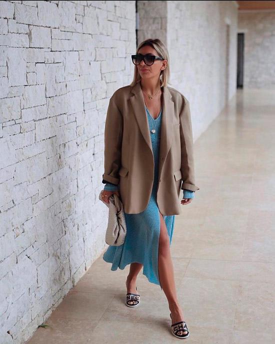 Девушка в легком голубом платье миди с разрезом спереди, блейзер оверсайс, образ дополняют простые шлепки и большие солнцезащитные очки