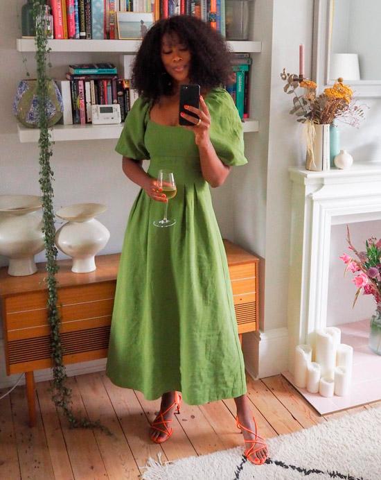 Девушка в летнем зеленом платье миди и оранжевых босоножках на ремешках