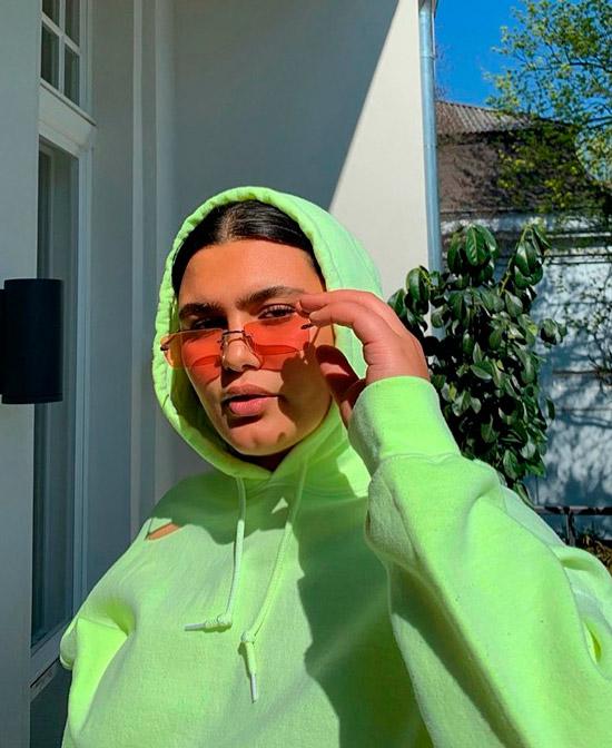 Девушка в неоновой зеленой толстовке и розовых солнцезащитных очках