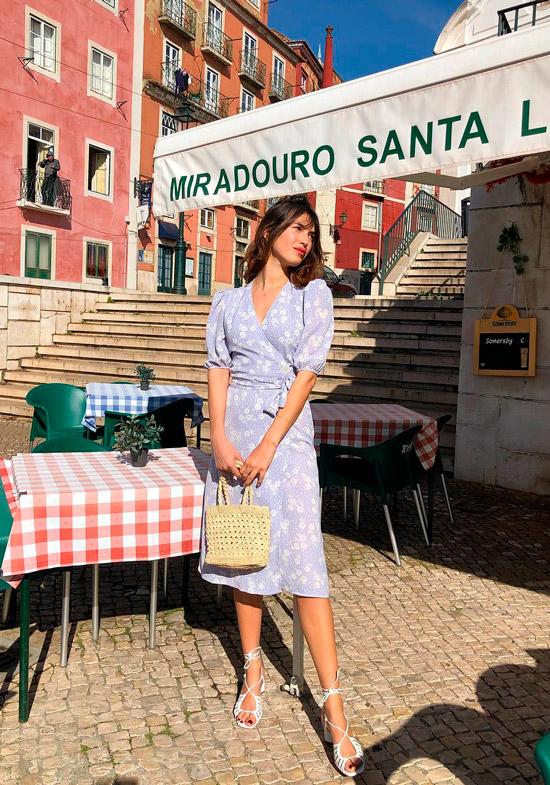 Девушка в нежном голубом платье с поясом на талии, белые босоножки на ремешках и сумочка