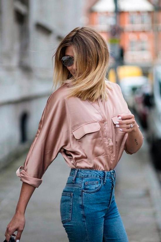 Девушка в простых джинсах с завышенной талией, нежная розовая рубашка из атласа, образ завершают солнцезащитные очки