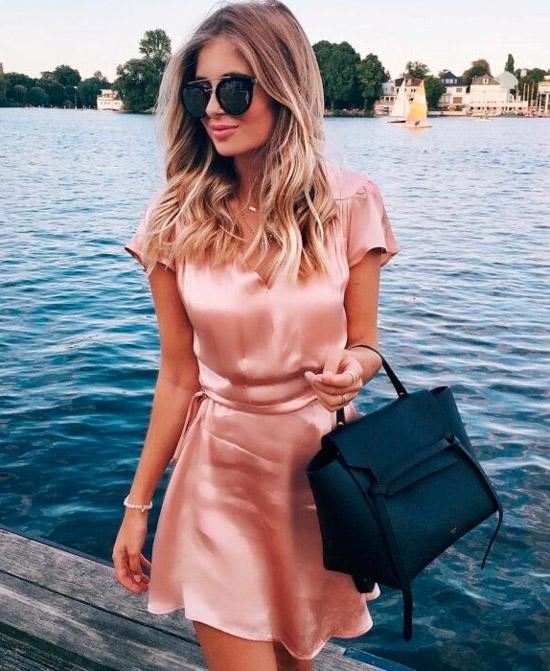 Девушка в романтичном розовом платье миди из атласа, образ дополняют черная сумка и солнцезащитные очки