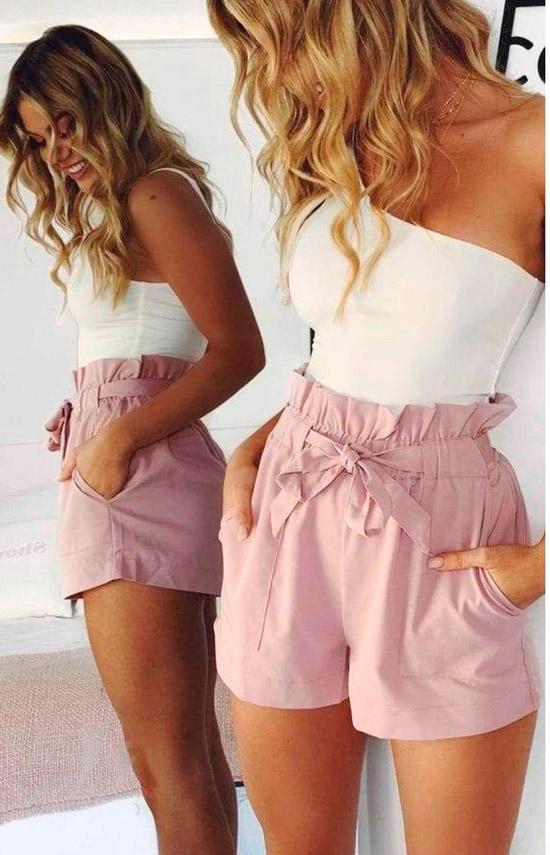 Девушка в розовых хлопковых шортах с высокой талией и белый топ на одно плечо