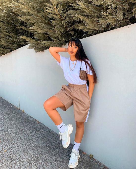 Девушка в спортивных бежевых шортах, белая футболка и кроссовки