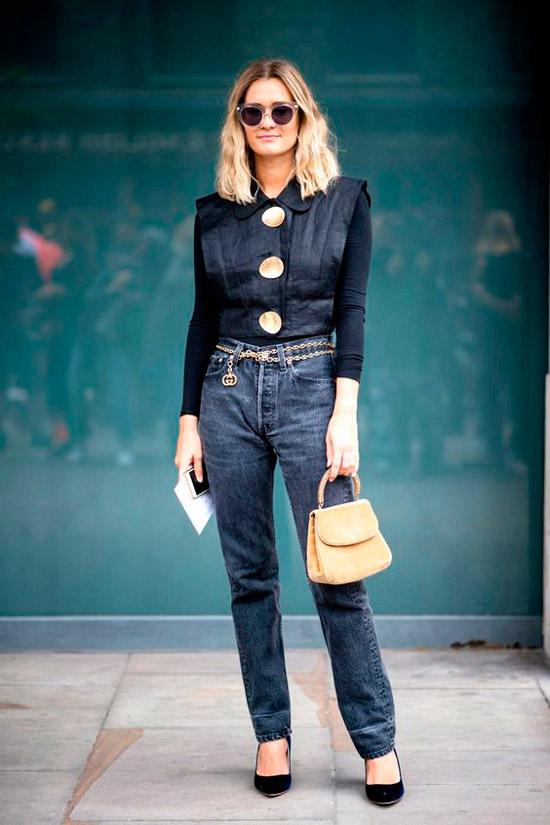 Девушка в темных джинсах с цепным ремнем, черная рубашка с большими пуговицами и черные туфли