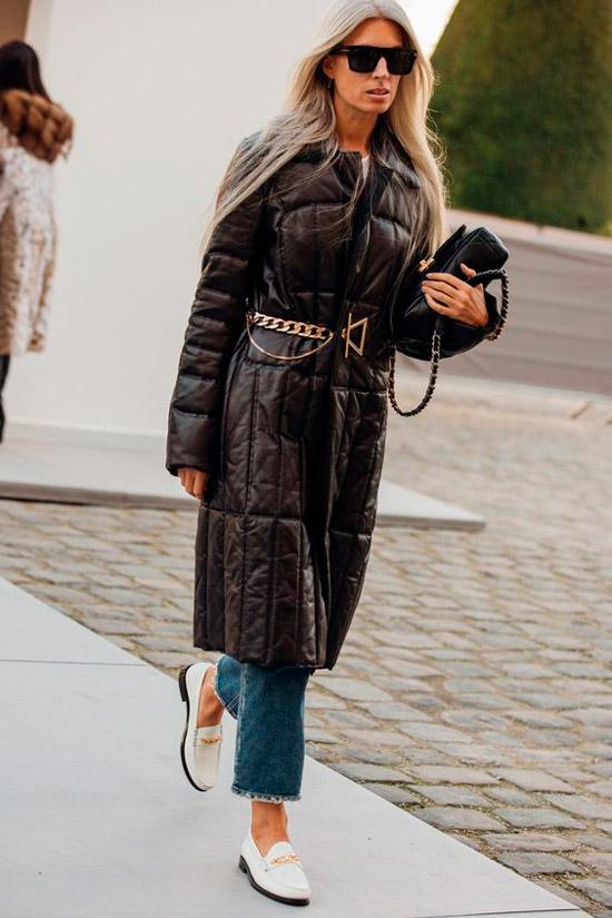 Девушка в укороченных синих джинсах, черное пальто с цепным поясом, образ завершают солнцезащитные очки и белые лоферы