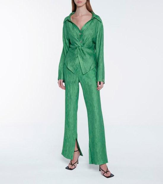 Девушка в зеленом костюме в складку с приталенной блузкой и штанами клеш