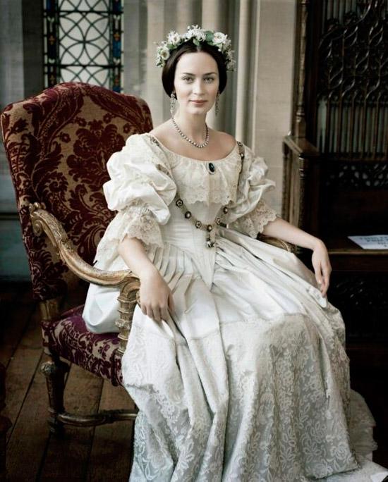 Эмили Блант в белом воздушном платье с кружевами и рюшами, образ дополняет ободок из цветов