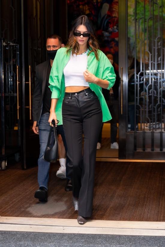 Кендалл Дженнер в черных брюках и зеленой рубашке