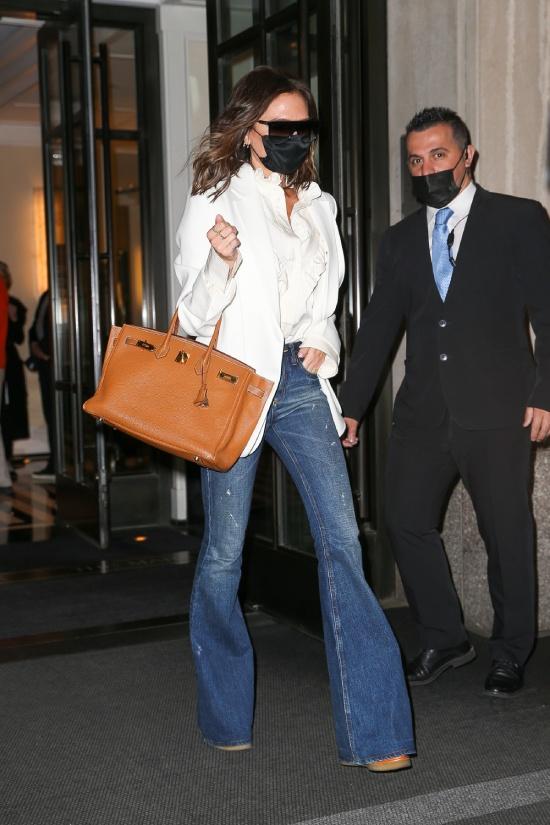 Виктория Бекхэм в белом пиджаке и коричневой сумкой