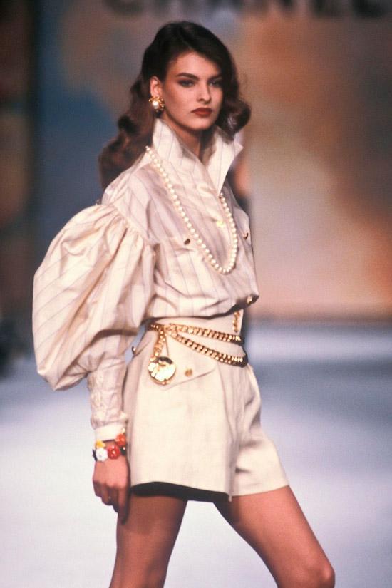Модель в бежевой рубашке с объемными рукавами, шорты песочного цвета с золотым цепным ремнем и украшения