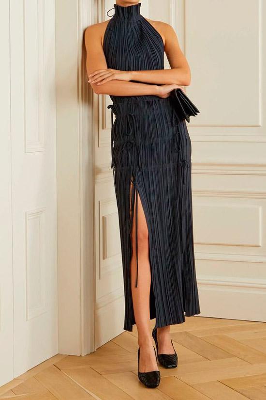Модель в черном вечернем платье в складку с глубоким разрезом до бедра