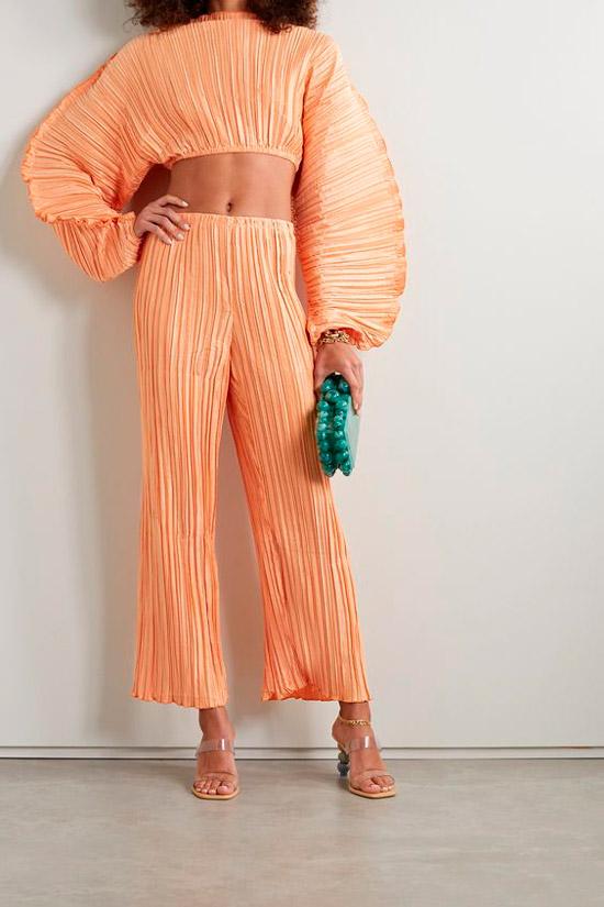 Модель в нежном персиковом костюме в складку с укороченным топом с объемными рукавами и свободные штаны