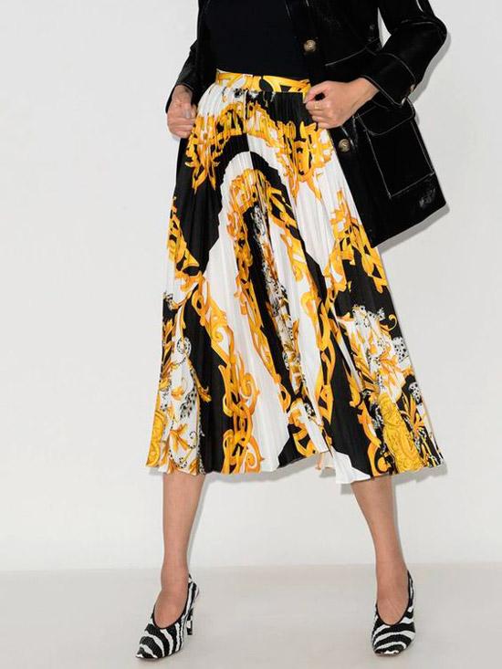 Модель в плиссированной миди юбке с принтом