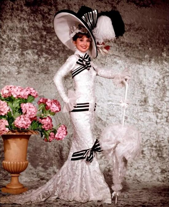 Одри Хепберн в неповторимом белом платье до пола с черными вставами и шлейфом, образ дополняет огромная шляпа