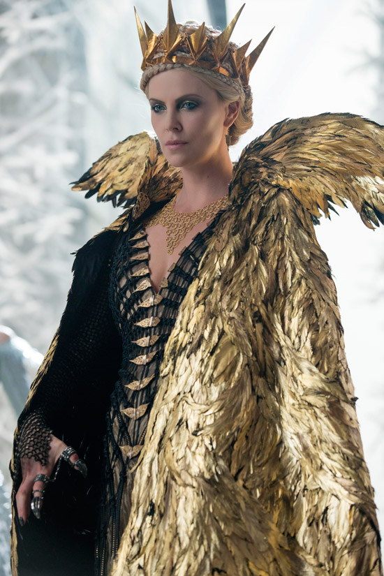 Шарлиз Терон в черном платье с золотой накидкой и короной