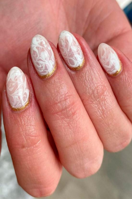 Белый мраморный маникюр с золотыми блестками на овальных ногтях