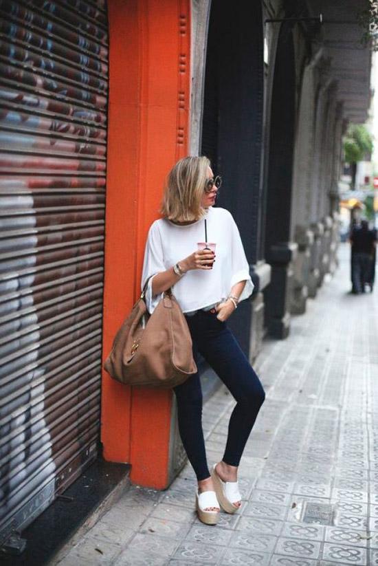 Девушка в облегающих джинсах, простая белая офта и сандалии на платформе