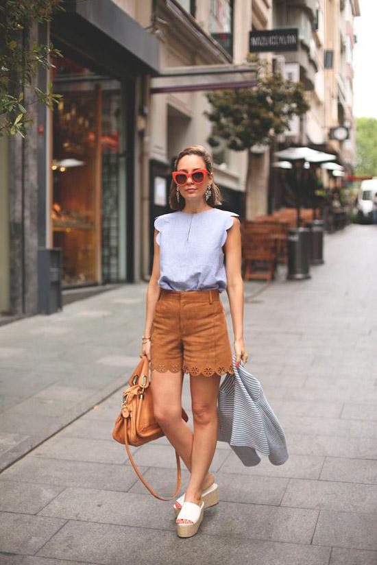 Девушка в коричневых замшевых шортах, нежная блуза и белые сандалии на платформе