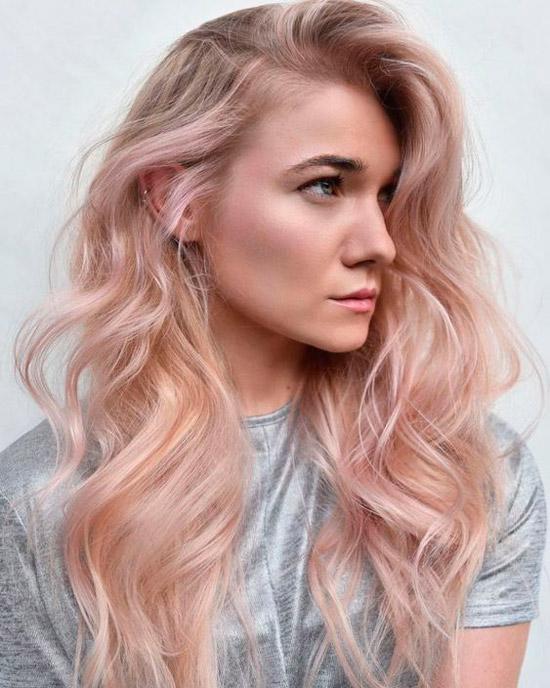 Девушка со светлыми волосами и нежными розовыми прядями на длинных волнистых волосах