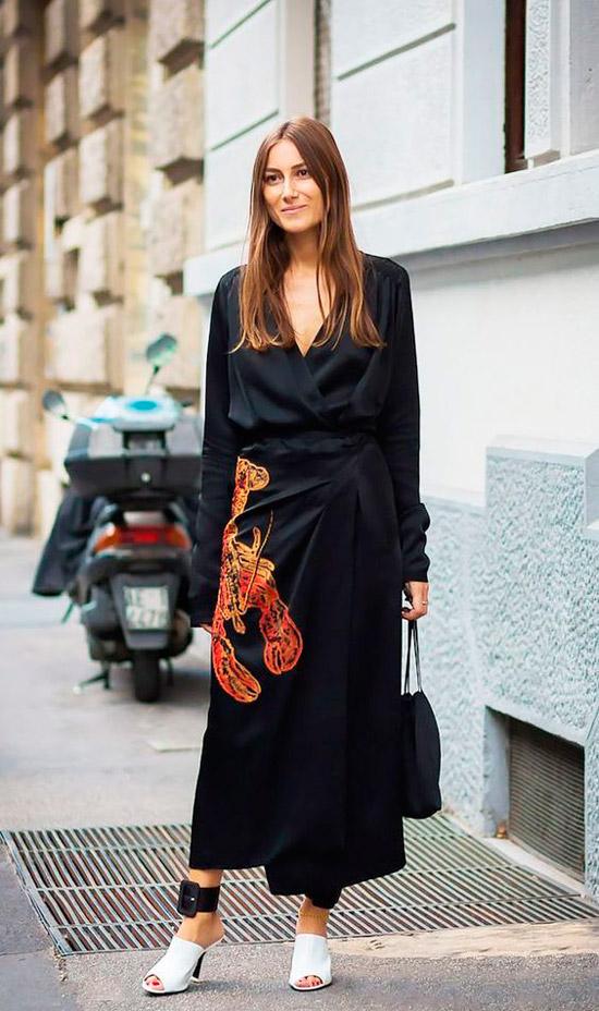 Девушка в черном платье с запахом и длинными рукавами, белые сабо и сумочка
