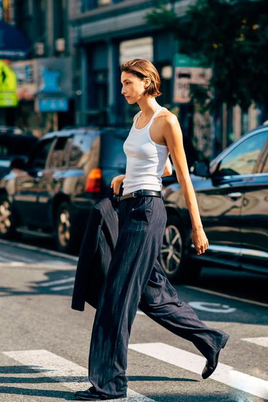 Девушка в черных свободных брюках, белая майка и ботинки
