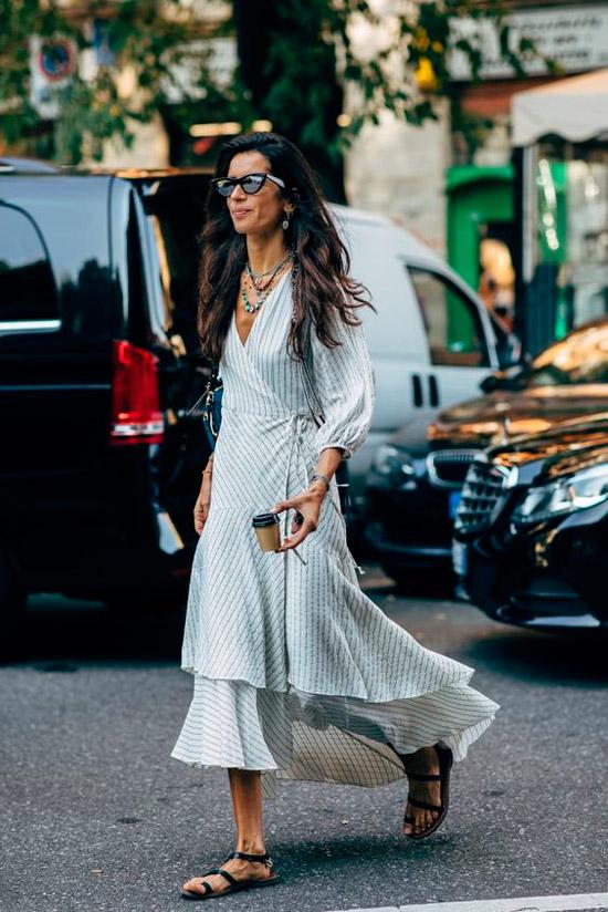 Девушка в легком платье с запахом, черные сандалии и солнцезащитные очки дополняют образ