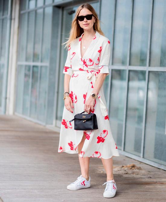 Девушка в летнем белом платье с запахом с цветочным принтом, белые кеды и черная сумочка завершают образ