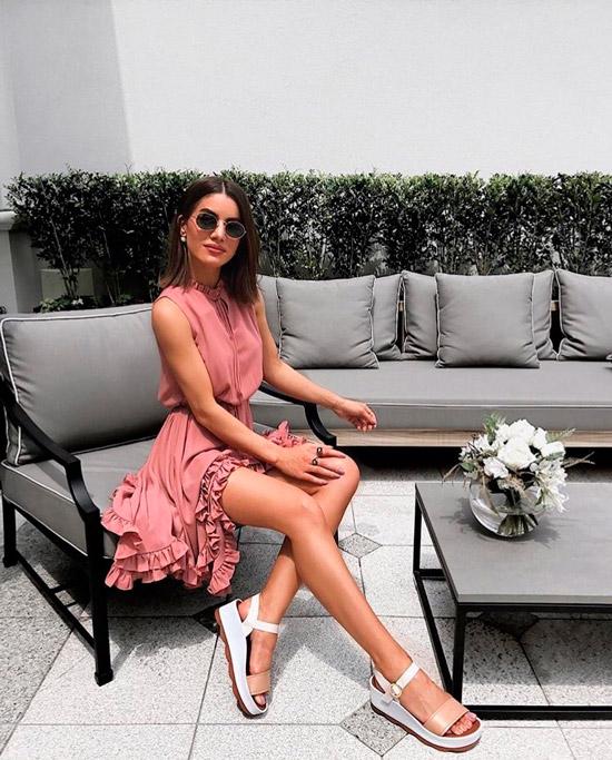 Девушка в нежном розовом платье с оборками и белые сандалии на платформе