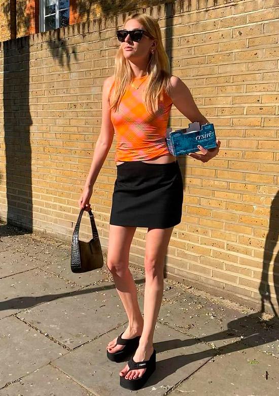 Девушка в оранжевом топе, черная мини юбка и сланцы на платформе