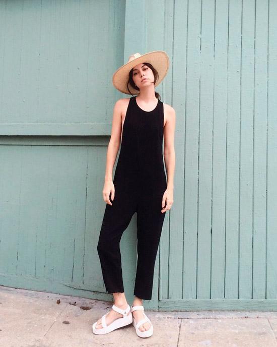 Девушка в простом черном комбинезоне, белые сандалии на платформе и соломенная шляпа