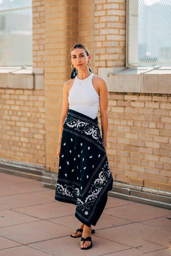 Девушка в простой белой майке, черная миди юбка с белым принтом, шлепки на плоской подошве