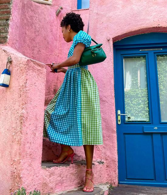 Девушка в романтичном платье в клетку и розовых босоножках на шпильке