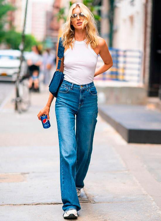 Девушка в синих джинсах клеш, белый топ и кроссовки