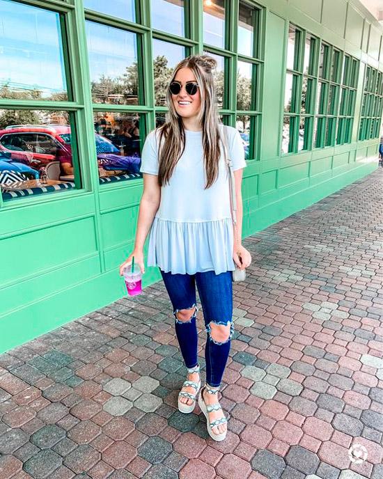 Девушка в синих узких джинсах с дырками, голубая футболка и сандалии на платформе
