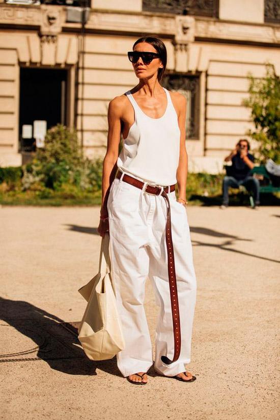 Девушка в свободных светлых брюках с ремнем, белый топ и шлепки