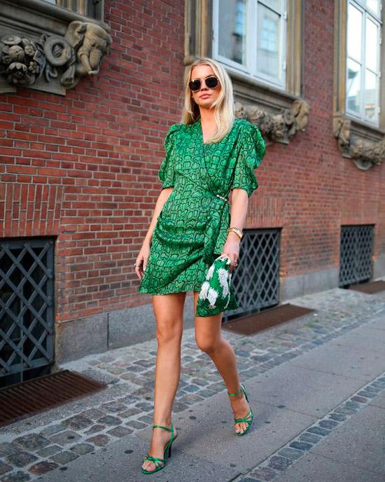 Девушка в зеленом мини платье с запахом и короткими рукавами, образ дополняют босоножки с ремешками и сумчка